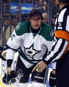 Dallas Stars left wing Ryan Garbutt gathers his equipment to leave the ice with a bloody face during the third period of an NHL hockey game against the Boston Bruins in Boston on Tuesday, Nov. 5, 2013. The Stars won 3-2 in a shootout. (AP Photo/Elise Amendola)