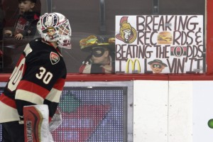 A fan holds a sign as Ottawa Senators goalie Andrew ìThe Hamburglarî Hammond skates pass during the warmup before NHL hockey game action against the Boston Bruins, Thursday, March 19, 2015, in Ottawa, Ontario. (AP Photo/The Candian Press, Adrian Wyld) ORG XMIT: AJW201