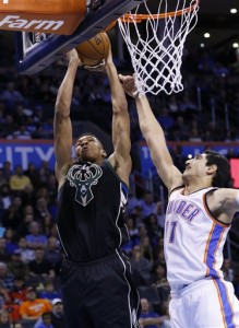 Milwaukee Bucks forward Giannis Antetokounmpo, left, dunks against the Oklahoma City Thunder center Enes Kanter (11) during the second quarter of an NBA basketball game in Oklahoma City, Tuesday, Dec. 29, 2015. (AP Photo/Alonzo Adams)