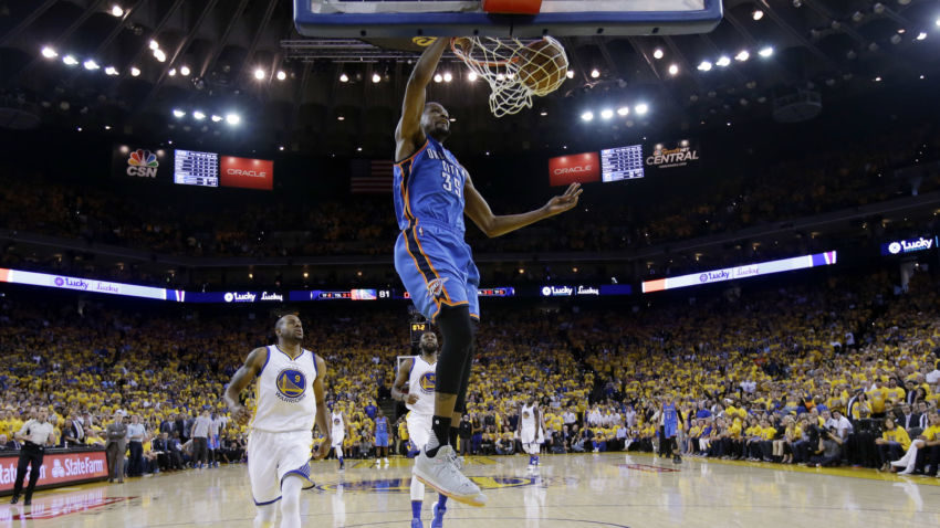 Oklahoma City Thunder's Kevin Durant (35) dunks past Golden State Warriors' Andre Iguodala (9) during the second half in Game 5 of the NBA basketball Western Conference finals Thursday, May 26, 2016, in Oakland, Calif. Golden State won 120-111. (AP Photo/Marcio Jose Sanchez)